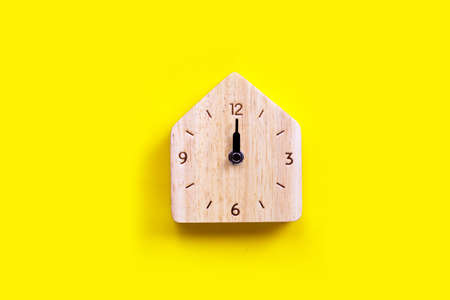 Miniature house wooden clock on yellow background. Copy space
