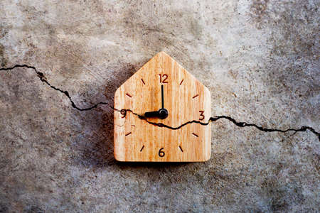 Wooden clock on cracked cement wall texture background. Top view Banco de Imagens
