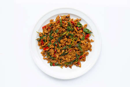 Thai food. Stir-fried minced pork with basil leaves on white background.