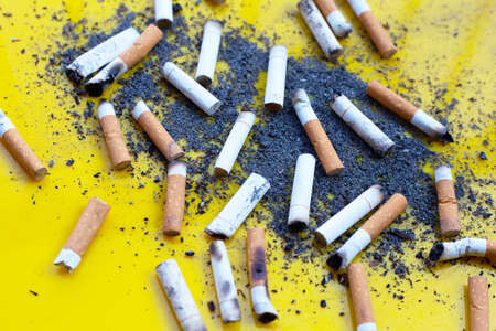 Cigarette butts on yellow background.