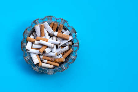 Cigarettes buds in a transparent ashtray on blue Stok Fotoğraf