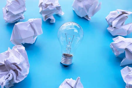 Light bulb with white crumpled paper on blue background. Ideas and creative thinking concept. Top view