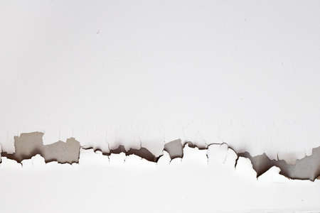 White color paint peeling off on ceiling house. Under the roof