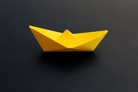 Yellow paper boat on dark background. Copy space