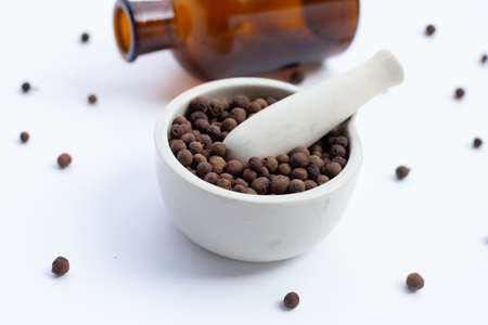 Allspice in porcelain mortar with pestle on white background.