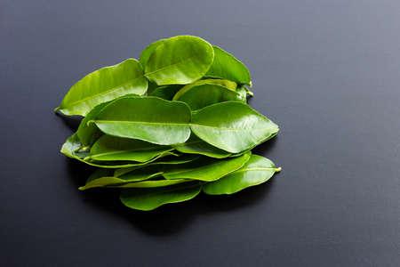 Bergamot kaffir lime leaves herb fresh ingredient on dark background.