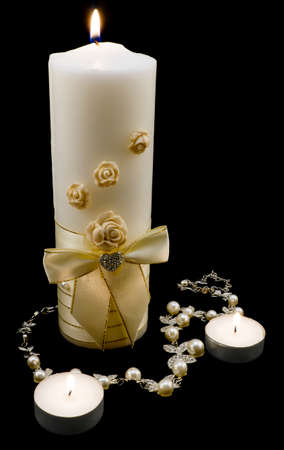 pearl: Wedding decoration: silver necklace with pearls and gold candles isolated on black Stock Photo