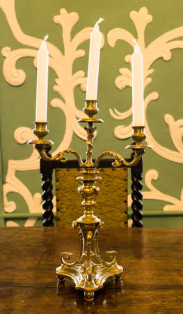 candlestick: Gold candlestick with candles on the table Stock Photo