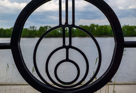 iron fence: Round fence, river and sky