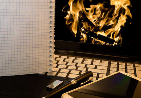 flash drive: Office workplace with notebook, smart phone, pen, flash drive and wordpad with burning fire background Stock Photo