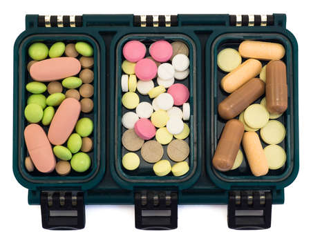 pillbox: Multi-colored pills in green box organizer isolated on white