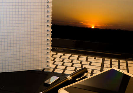 flash drive: Office workplace with notebook, smart phone, pen, flash drive and wordpad with sunset background