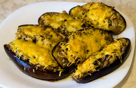 queso rayado: Boats of zucchini stuffed with meat, rice, tomato and mushrooms with grated cheese on white plate
