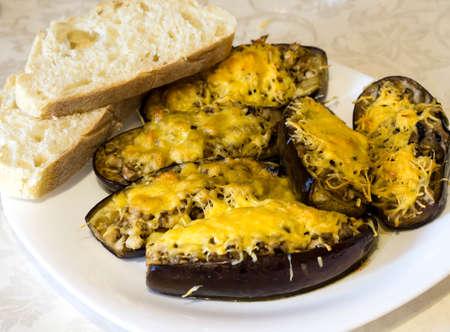 queso rallado: Barcos de calabacín rellenas de carne, arroz, tomate y champiñones con queso rallado con pan en un plato blanco