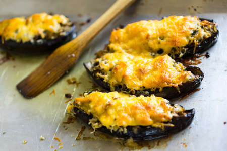 grated cheese: Boats of eggplant zucchini stuffed with meat, rice, tomato and mushrooms with grated cheese on baking tray Foto de archivo