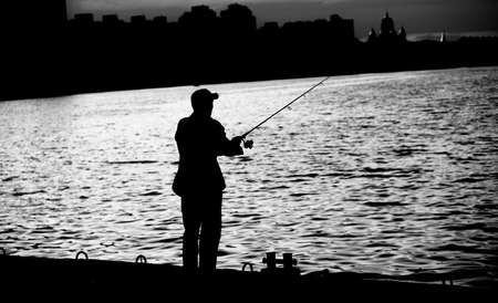 fishing reel: Fisherman standing on edge of dock with fishing rod near river in city black and white Stock Photo