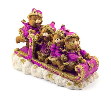 osos navideños: Hecho a mano de Navidad lleva en trineo en violeta y oro chaquetas y sombreros en la nieve aislada en blanco Foto de archivo