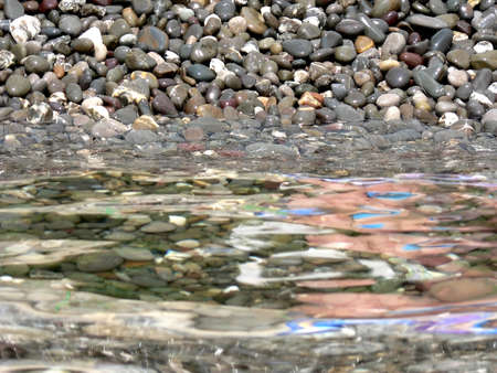 sea water: Stones on background of sea water with reflections Stock Photo