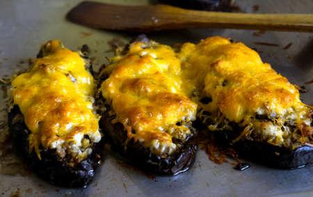grated cheese: Barcos de calabac�n berenjena rellenos de carne, arroz, tomate y champi�ones con queso rallado en la bandeja de hornear