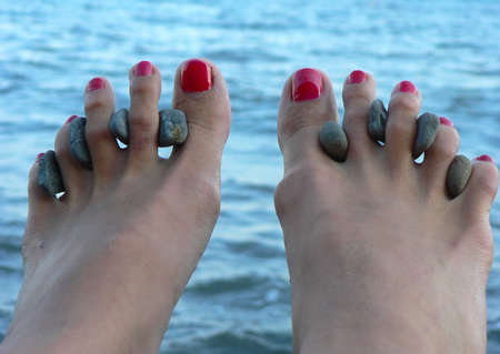 painted toes: Female legs on sea procedures with curative stones between fingers
