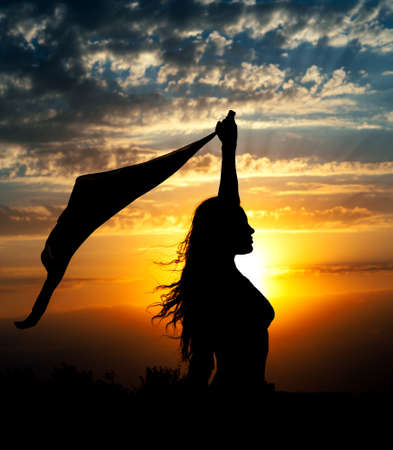 beauty body: Young girl silhouette with shawl on  beautiful cloudy sky with red sunset and rays of light