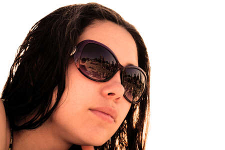 girl  care: Face of young brunette girl in sunglasses with beach reflection in bright sun rays warm filtered