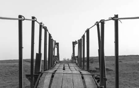tension: Tension bridge stretching into sunset black and white Stock Photo