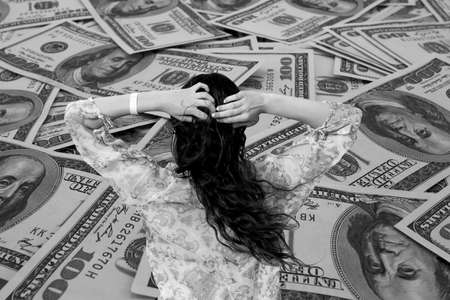pareo: Money problem: Young brunette girl in bikini and pareo on background of mount of hundred dollar banknotes black and white Stock Photo