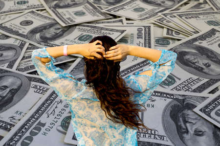 million dollars: Money problem: Young brunette girl in bikini and pareo on background of mount of hundred dollar banknotes filtered Stock Photo