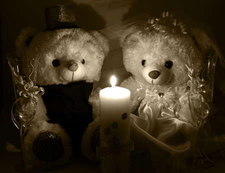 selebration: Wedding setting: hand made teddy boy and girl, white and gold candle, wedding glasses by candlelight brown filtered