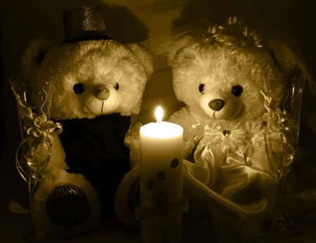 selebration: Wedding setting: hand made teddy boy and girl, white and gold candle, wedding glasses by candlelight warm filtered