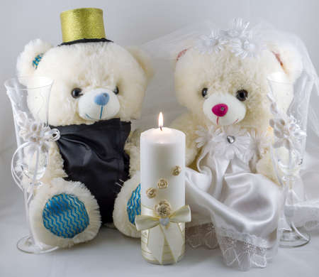 selebration: Wedding setting: hand made teddy boy and girl, white and gold candle, wedding glasses Stock Photo