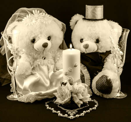 Wedding setting: hand made boy and girl teddies, white and gold candle, wedding glasses and pearl silver necklace in form of heart on textured background warm filtered