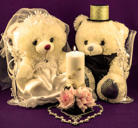 gold textured background: Wedding setting: hand made boy and girl teddies, white and gold candle, wedding glasses and pearl silver necklace in form of heart on textured violet background warm filtered