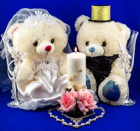 selebration: Wedding setting: hand made boy and girl teddies, white and gold candle, wedding glasses and pearl silver necklace in form of heart on textured blue background Stock Photo
