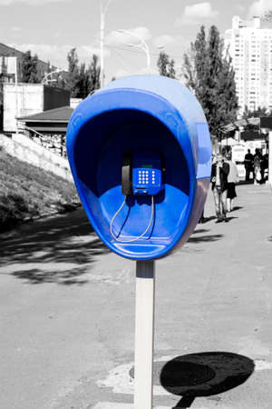 pillar box: Pillar with blue public telephone set on city street black and white styled