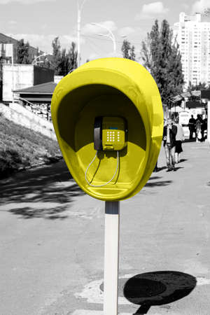 pillar box: Pillar with the yellow public telephone set on city street black and white styled