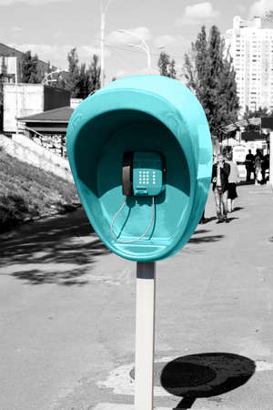 pillar box: Pillar with cyan public telephone set on city street black and white styled Stock Photo