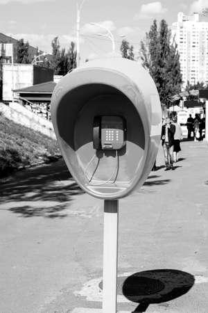 pillar box: Pillar with public telephone set on city street black and white Stock Photo