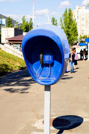 pillar box: Pillar with blue public telephone set on city street Stock Photo