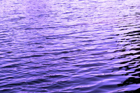Violet water with sun reflections background texture