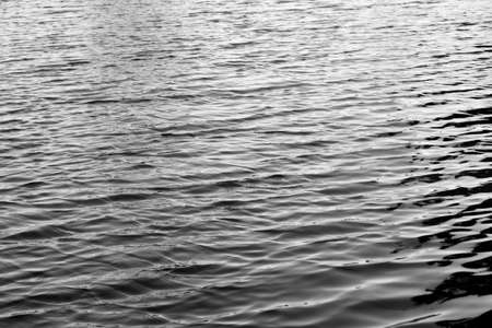 deflection: Water with sun reflections background texture black and white Stock Photo