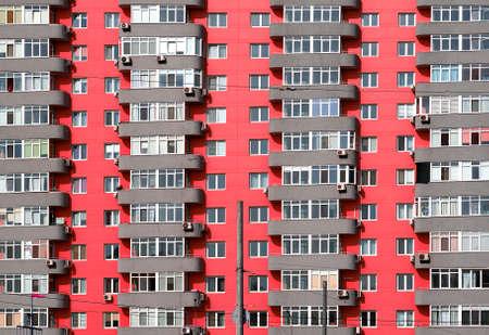 many windows: Pink and grey brick house with many windows and balcony background