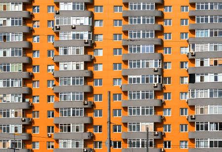 many windows: Orange and grey brick house with many windows and balcony background