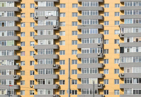 many windows: Beige and grey brick house with many windows and balcony background Stock Photo