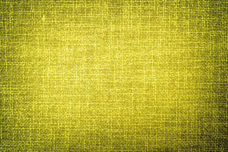 contrasted: Old yellow cloth texture high contrasted with vignetting effect