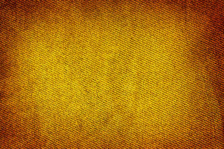 vignetting: Yellow gold fabric woven texture high contrasted with vignetting effect macro background Stock Photo