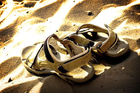 contrasted: Marching sandals on beach sand high contrasted with vignetting effect