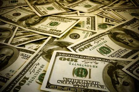 cuenta: Monte de cientos de billetes de dólar textura de fondo cálido filtrada alto contraste con viñetas de efecto Foto de archivo
