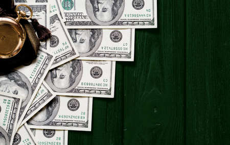 laid: Stack of money dollars laid out like a ladder with antique gold watch on dark green retro stylized wood background